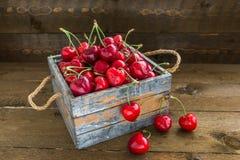 Le ciliege con le gocce di acqua è in scatola di legno d'annata Fotografia Stock Libera da Diritti