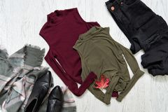 Le cime colorano cachi e Borgogna Jeans neri, una sciarpa e stivali concetto alla moda Immagini Stock