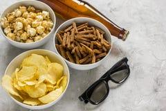 Le cinéma et la TV whatching avec de la bière, des miettes, des frites et le maïs de bruit lapident le fond Photographie stock libre de droits