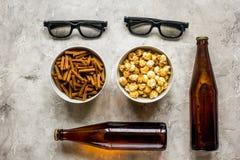 Le cinéma et la TV whatching avec de la bière, les miettes et le maïs de bruit lapident la vue supérieure de fond Images stock