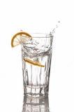 Le citron éclabousse dans un verre d'eau Photos libres de droits