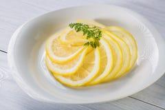 Le citron coupé en tranches rapièce avec des herbes du plat blanc et de la table en bois blanche Photographie stock