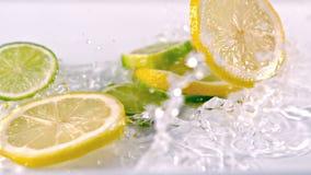 Le citron découpe la chute en tranches dans l'eau banque de vidéos