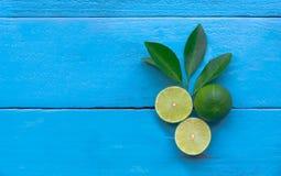 le citron de chaux sont demi coupe sur le fond en bois bleu Copiez Spac Photo libre de droits