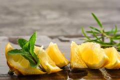 Le citron et les feuilles en bon état ont servi sur le panneau en bois de cuisine sur la table concrète, l'ingrédient pour des co Images libres de droits