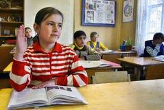 Le classi nella scuola del villaggio, scolara solleva la sua mano Fotografia Stock