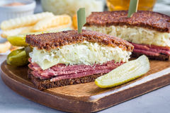 Le classique reuben le sandwich, servi avec le pickle à l'aneth, des pommes chips, horizontales Photographie stock libre de droits