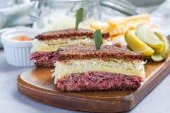 Le classique reuben le sandwich, servi avec le pickle à l'aneth, des pommes chips, horizontales Photos stock