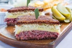 Le classique reuben le sandwich, servi avec le pickle à l'aneth, des pommes chips, horizontales Image stock