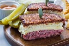 Le classique reuben le sandwich, servi avec le pickle à l'aneth, des pommes chips, horizontales Photo stock