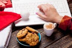 Le clavier émouvant de main femelle près de la tasse de café, plaquent complètement de Images stock