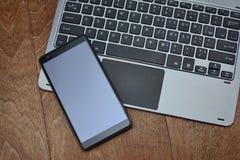 Le clavier de l'ordinateur portable et le smartphone se trouvent sur la surface en bois image libre de droits