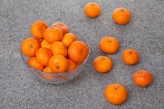 Le clementine fresche fruttificano con la ciotola di vetro sulla pietra Fotografie Stock