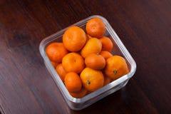 Le clementine fresche fruttificano con la ciotola di vetro sulla tavola di legno Fotografia Stock