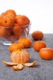 Le clementine fresche fruttificano sbucciato con la ciotola di vetro nel verticale Fotografia Stock