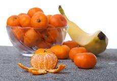 Le clementine fresche fruttificano sbucciato con la ciotola di vetro nel verticale Immagini Stock