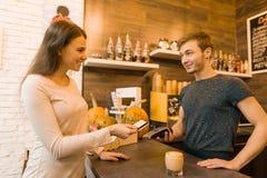 Le client de café de fille paye le café par la carte de crédit, barman tenant une machine de lecteur de carte de crédit photographie stock libre de droits