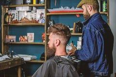 Le client de hippie a obtenu la nouvelle coupe de cheveux Coiffeur avec l'homme barbu regardant le miroir, fond de raseur-coiffeu photographie stock libre de droits