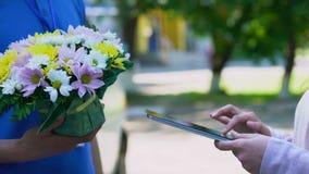Le client de société de livraison apposant la signature sur le comprimé et la recevant fleurit banque de vidéos