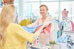 Le client et le vendeur dans le magasin d'habillement photographie stock libre de droits