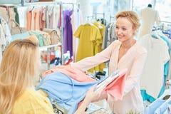 Le client et le vendeur dans un magasin d'habillement photos libres de droits