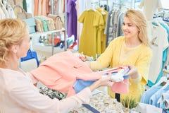 Le client et le vendeur dans un magasin d'habillement photo libre de droits