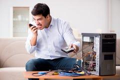 Le client fâché essayant de réparer l'ordinateur avec l'appui de téléphone Photo stock