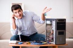 Le client fâché essayant de réparer l'ordinateur avec l'appui de téléphone Images stock