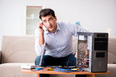Le client fâché essayant de réparer l'ordinateur avec l'appui de téléphone Image libre de droits