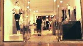Le client féminin Defocused et les ventes auxiliaires dans les bas font des emplettes dans un centre commercial moderne banque de vidéos