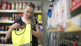 Le client féminin examine un gilet de signal pour des conducteurs dans une boutique clips vidéos