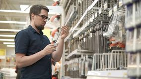 Le client masculin prend le grand peu de foret en métal des supports dans une boutique pour des constructeurs banque de vidéos