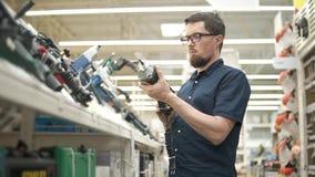 Le client masculin vérifie un marteau dans une boutique des outils de bâtiment banque de vidéos