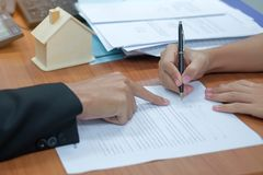 le client signe le contrat de prêt immobilier avec le vrai agent immobilier image libre de droits