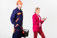 Le client trompe le dépanneur, constructeur, mécanicien Le réparateur, constructeur veut le salaire Image stock
