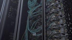 Le clignotant de support de serveur a mené des lumières sont à un centre de traitement des données moderne sont situés derrière u banque de vidéos