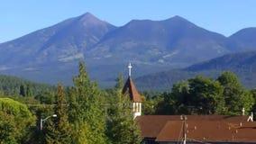 Le clocher et les pins d'église atteignent vers le haut contre un contexte des montagnes banque de vidéos