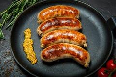 Le closeip de vue supérieure a fait frire des saucisses sur la casserole ronde avec de la moutarde granulaire images libres de droits