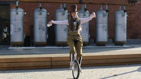 Le clown de jeune fille monte un monocycle et jongle des boules clips vidéos