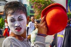 Le clown de rue est dans l'action sur son étape, la rue Photo libre de droits