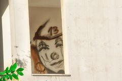 Le clown numéro dessiné par visage 13 sur son front dans la fenêtre d'une maison abandonnée images stock