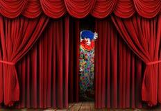 Le clown rampant regardant par le rideau en étape drape Photos stock