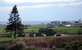 Le club et le terrain de golf de golf de côte dans peu de baie au coucher du soleil Photo libre de droits