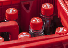 Le coca-cola met des supports en bouteille dans une boîte rouge images libres de droits
