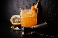 Le cocktail alcoolique de couleur orange avec de la glace et l'agrume se tient sur un fond noir images libres de droits