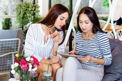 Le cocktail blanc numérique de fleurs d'été de filles d'achat de café du comprimé deux d'Internet en ligne de jeunes femmes heure Photo libre de droits