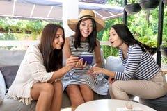 Le cocktail blanc numérique de fleurs d'été de filles d'achat de café du mobile trois de téléphone d'Internet en ligne de jeunes  Photo stock