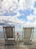 Le cocktail rouge sur la table blanche a placé au-dessus de l'océan photographie stock libre de droits