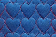 Le coeur abstrait de fond sur des textiles, les fils rouges a piqué des points sous forme de coeurs sur le coton bleu, denim photos stock