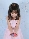Le coeur admiratif de petite fille forme dans des ses mains Image stock